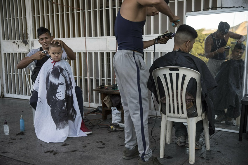 Juan Manuel Marquez, 32, left, cuts the hair of Jean Pierre, 4, at a makeshift barber shop on a sidewalk in Caracas, Venezuela.